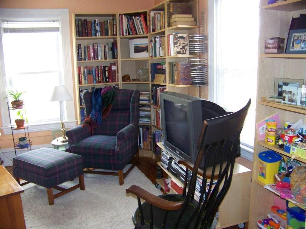 The sunny living room has lots of bookshelves and space for relaxing