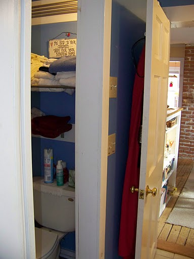 The toilet area offers privacy and some extra storage for towels