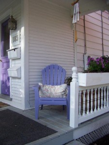 The front porch has purple chairs to match the front door!